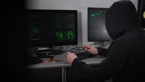 Back view of a hooded hacker making cyber attack on bank network. Man in black is typing fast on keyboard and stealing. Back view of a hooded hacker making cyber stock video footage