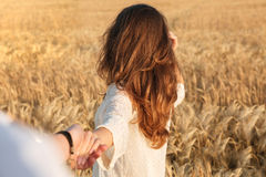 Back view image of amazing young lady in the field. Looking aside holding your hand royalty free stock photo