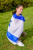 Back view jewish girl with Israeli flag wrapped around her. Teenager patriot jewish girl sitting with the flag of Israel wrapped around her. Memorial day-Yom royalty free stock photo