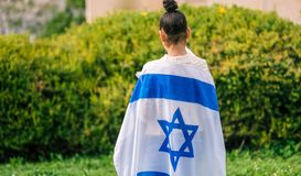 Back view jewish girl with Israeli flag wrapped around her. Teenager patriot jewish girl standing with the flag of Israel wrapped around her. Memorial day-Yom royalty free stock photography