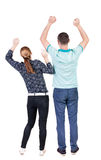 Back view of  joyful couple celebrating victory hands up. Royalty Free Stock Photo