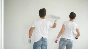 Back View of Joyful Couple Doing Apartment Repair Together. Young Wife and Husband Paints the Wall with White Paint. stock video footage