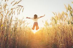 Back view of jumping girl in the barley farm. Stock Photo