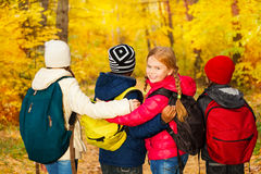 Back view of kids group stand close with rucksacks Stock Image