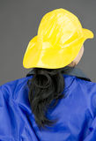 Back view of a lady firefighter in blue protective suit wearing yellow helmet Royalty Free Stock Image