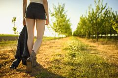 Low angle on legs of anonymous country girl, who is walking by the path in the green fruit orchard, she is wearing brown boots and. Back view on legs of stock photography