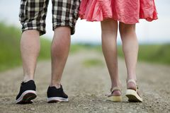 Back view of legs of young slim woman in red dress and man in shorts walking together by ground road on sunny summer day on. Blurred background stock photography