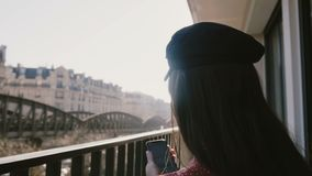 Back view lens flare close-up, happy beautiful elegant woman using smartphone at idyllic sunny morning Paris balcony. stock footage