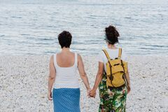 Back view of lesbian couple holding hands at the beach during sunset. Love is love and LGTBI concept