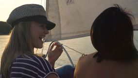 Back view of lesbian couple hugging on sailboat floating on river at sunset. Young people on vacation. lgbt, gay family, summer holidays stock footage