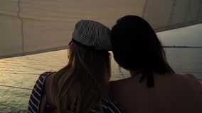 Back view of lesbian partners hugging on sailboat and watching sunset. Young people on vacation. lgbt, gay couple, summer holidays stock video