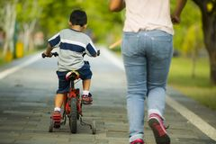 Back view lifestyle portrait of mother and young happy son at city park having fun together the kid learning bike riding and the. Women running after the child royalty free stock images