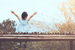 Back view of little asian child girl raise her arms sitting. And looking at nature together in vintage color tone Stock Photo