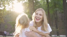 Back view of little blond girl running towards her mother in the sunshine. Attractive young woman hugging her daughter