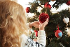 Back view of little blonde girl helping her mother decorating Ch. Ristmas tree, holding red bauble, indoor Royalty Free Stock Image