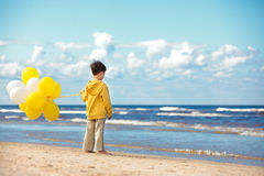 Back view of little boy with ballons on the beach Stock Image