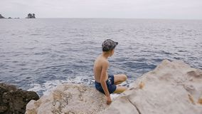 Back view. Little boy in shorts with cap sits on the stony beach in the rocky bay on a sunny day. Small child looks on stock video