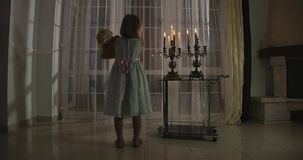 Back view of little Caucasian girl standing in candlelight with doll. Child caressing her toy and looking at window