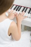 Back view of little child in white dress playing piano Royalty Free Stock Photography