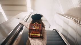 Back view of little cute girl moving upstairs on the escalator. Child clothing the french style going to school. Attractive alone kid going up on moving stair stock video footage