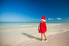 Back view of Little cute girl in red hat santa. Claus on the beach. This image has attached release Stock Photos