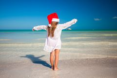 Back view of Little cute girl in red hat santa. Claus on the beach. This image has attached release Royalty Free Stock Image