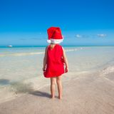 Back view of Little cute girl in red hat santa. Claus on the beach. This image has attached release Royalty Free Stock Photography