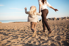 BACK VIEW: Little daughter runs with his mother on a beach Royalty Free Stock Images