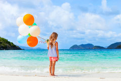 Back view of little girl with balloons at beach. Back view of little girl with colorful balloons at beach during summer vacation Royalty Free Stock Photography