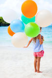Back view of little girl with balloons at beach. Back view of little girl with colorful balloons at beach during summer vacation Royalty Free Stock Photos