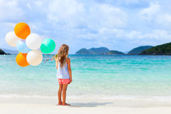 Back view of little girl with balloons at beach Royalty Free Stock Photography