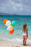 Back view of little girl with balloons at beach. Back view of little girl with colorful balloons at beach during summer vacation Royalty Free Stock Image