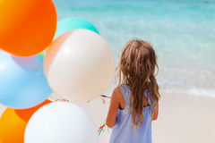 Back view of little girl with balloons at beach Royalty Free Stock Image