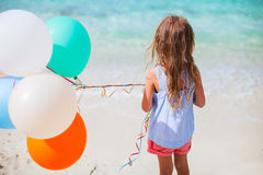 Back view of little girl with balloons at beach. Back view of little girl with colorful balloons at beach during summer vacation Royalty Free Stock Images