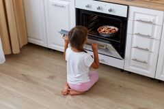 Back view of little girl child waiting for baking croissant, muffins or cupcakes near oven, looking inside the oven while sitting