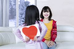 Girl giving her mom a greeting card. Back view of a little girl giving her mom a greeting card with a heart symbol, shot at home Royalty Free Stock Photos