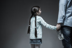 Back view of little girl holding her father hand. Think about future. Sad daughter wearing jeans skirt and striped shirt having two long braids putting her hand Stock Photos