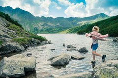 Back view of little girl jumping from stone to stone. In the Tatra Mountains Stock Image
