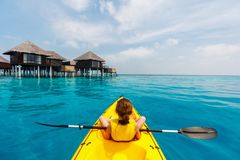 Little girl kayaking. Back view of little girl on a kayak at tropical lagoon Stock Photo