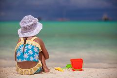 Back view of little girl playing on sandy beach Stock Images