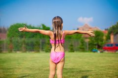 Back view of little girl in a swimsuit playing and Stock Images