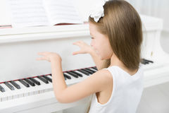 Back view of little girl in white dress playing piano Royalty Free Stock Images