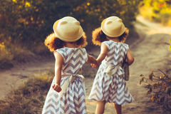 Back view of little girls sisters twins holding hands. Love, friendship concept. Back view of little girls sisters twins holding hands. Love, happy , friendship Royalty Free Stock Photos