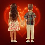 Back view of little kids holding hands. Back view of little girl and boy holding hands. Love, friendship, Valentine's Day concept Stock Image