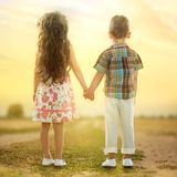 Back view of little kids holding hands at sunset Royalty Free Stock Photos