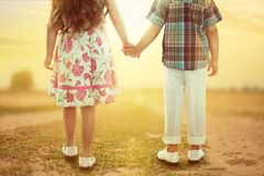 Back view of little kids holding hands at sunset Royalty Free Stock Images