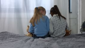 Back view little multi ethnic girls sitting on bed. Back view of little multi ethnic girls with plush toys sitting on bed and reading book in bedroom. Rear view stock video