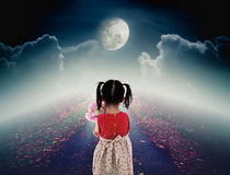 Back view of lonely child with doll sad gesture on pathway with. A nightly sky and a large moon for halloween background. The moon were NOT furnished by NASA Stock Image