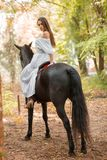 Back view. Long-haired brunette riding a black horse. Royalty Free Stock Image