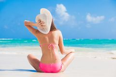 Back view of long haired girl in bikini and straw hat on tropical caribbean beach Royalty Free Stock Photography